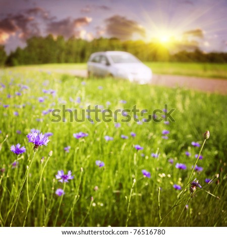 Sunset landscape with car on background. - stock photo