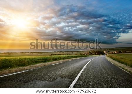 Sunset landscape with coastal road - stock photo