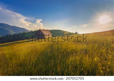 Sunset landscape with old rural house in the Carpathian mountains.  - stock photo