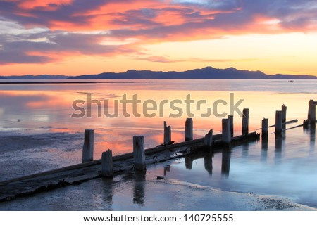 Sunset landscape with wooden posts at the Great Salt Lake, Utah, USA. - stock photo