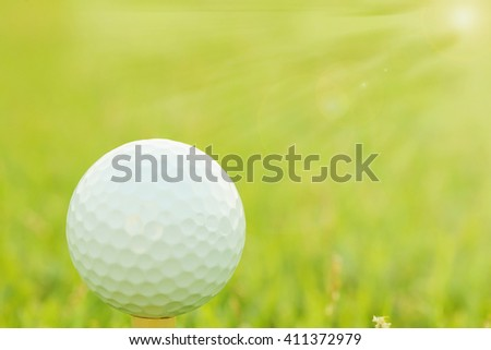 Sunset light at Golf ball on green grass. ( selective focus with lens flare effect) - stock photo