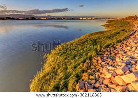 sunset light over river and beach with grass and rocks - stock photo