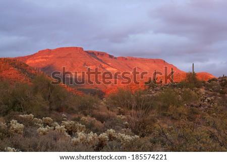 Sunset lights a large mesa in the Sonoran Desert near Phoenix, Arizona. - stock photo