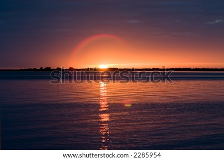 Sunset looking over Tampa Bay with reflection on water and lens flare halo around sun - stock photo