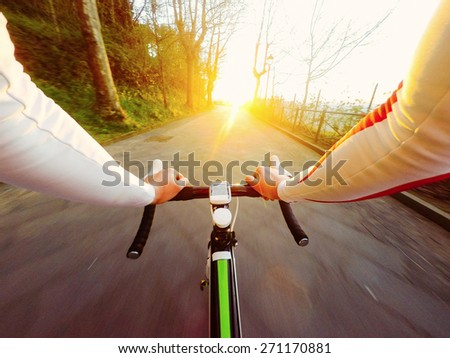Sunset, man on road bike. POV, Original Point of View.