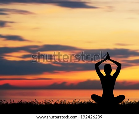 Sunset meditation. Silhouette of a woman doing yoga exercise in the evening. - stock photo