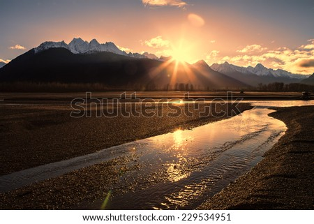 Sunset near the Chilkat River in Southeast Alaska with snow covered mountains in the background. - stock photo