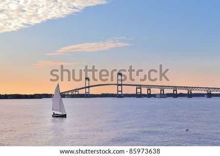Sunset Newport Bridge sailboats Newport Rhode Island USA. Person in sailboat is in silhouette also changed face and body shape, clothing, hair (person was bald) so they are totally unrecognizable - stock photo