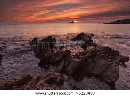 Sunset next to the Mewstone, Wembury, Devon, UK - stock photo