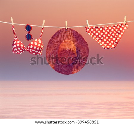 Sunset ocean vacation. Summer Beach clothes and accessories stylish set. Fashion swimsuit bikini red polka dots, sunglasses hat. Essentials creative look on tropical sea sky background.Vintage  - stock photo