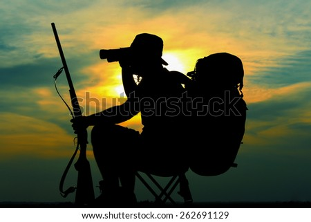 Sunset of Hunter with trigger, hat and backpack looking through binoculars - stock photo