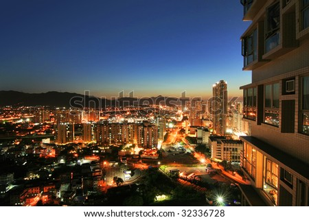 Sunset of Yuen Long, Hong Kong. Cityscape view with an apartment building at the right of the foreground. Low-rise buildings and houses surrounded by hills and traffic road. - stock photo