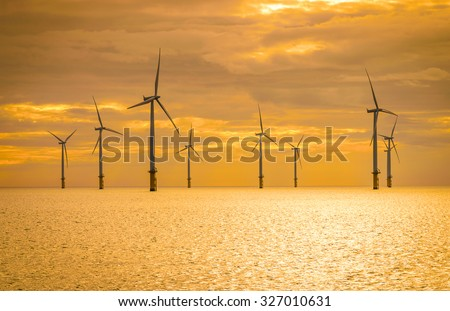 Sunset Offshore Wind Turbine in a Wind farm under construction off the England coast - stock photo