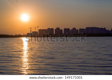 Sunset on a background of high-rise buildings and construction sites