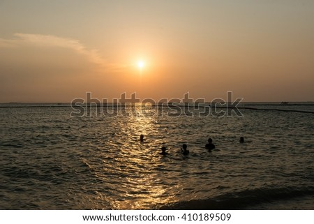 Sunset on a beach in a tropical country with unidentified people in the background - stock photo