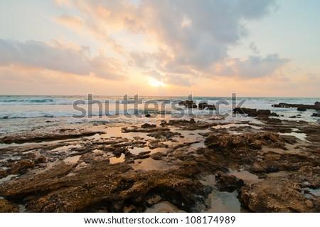 Sunset on a rocky beach, Israel - stock photo
