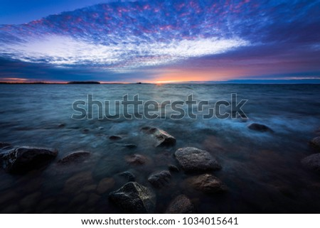 sunset on a rocky beach with waves rushing in