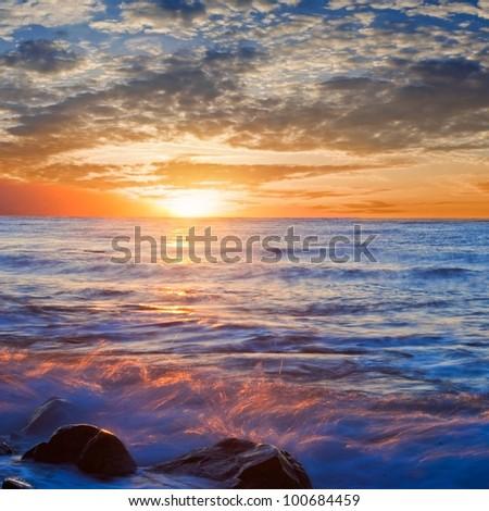 sunset on a sea coast - stock photo