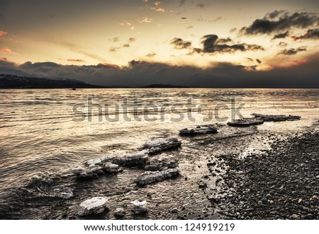 Sunset on an Alaskan beach with ice chunks in the water and interesting colorful clouds. - stock photo