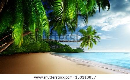 sunset on beach Anse Takamaka of Mahe island, seychelles  - stock photo