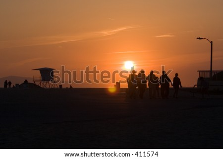 Sunset on beach with people - stock photo