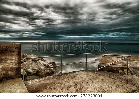 Sunset on breakwater with stairs on the Mediterranean sea with red steel lookout and green top white lighthouse in the cloudy background near Porec in Croatia - stock photo