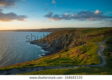 Sunset on Cornish cliffs, ocean and foot patch in wild scenery, English seascape - stock photo