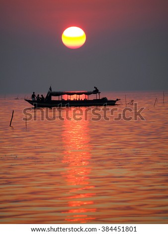 Sunset on floating, fishing village on the lake in Cambodia - stock photo