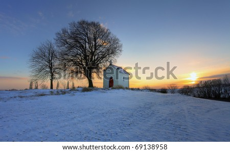 Sunset on frozen field with a chapel and clouds - stock photo