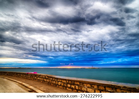Sunset on inflatable mattress on parapet in front of the Mediterranean sea with red steel lookout in the cloudy background near Porec in Croatia - stock photo