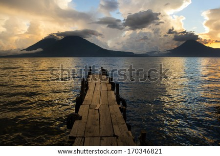 Sunset on Lake Atitlan with volcano in background - stock photo
