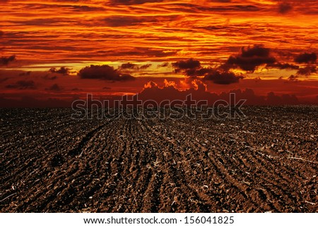 Sunset on landscape plowed field