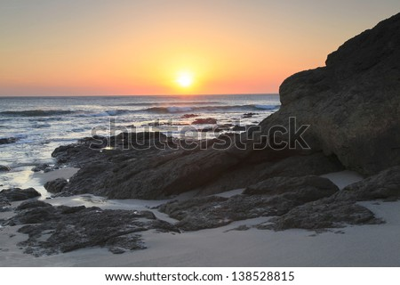 Sunset on Lava Covered Beach on Pacific Ocean Coast of Costa Rica - stock photo