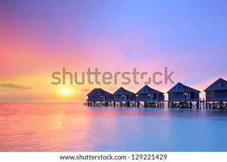 Sunset on Maldives island, water villas resort - stock photo