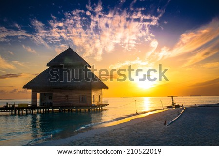 Sunset on Maldives island, water villas resort - stock photo