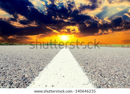 Sunset on old and lonely road - stock photo