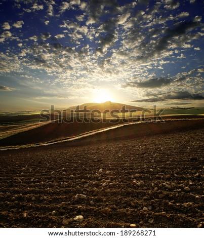 sunset on plowed land - stock photo