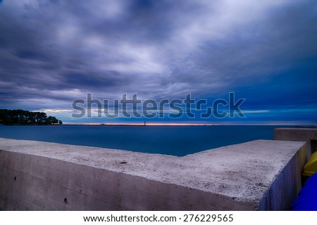 sunset on prefabricated breakwater on the Mediterranean sea with green top white lighthouse in the cloudy background near Porec in Croatia - stock photo