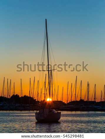 Sunset on the Adriatic Sea in Croatia, with boats profiled on warm evening light