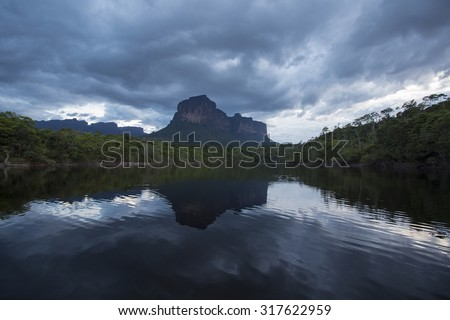 Sunset on the Auyantepui mountain in the Canaima National Park and its reflection in the water of the Gauja river. Bolivar State, Venezuela 2015 - stock photo