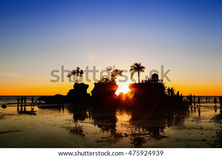 Sunset on the beach of Boracay Island with  silhouette of rock and people. White beach, Boracay, Philippines