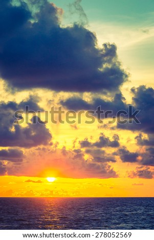 Sunset on the beach with cloud on sky - vintage filter - stock photo