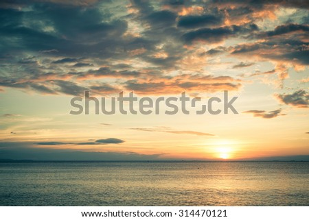 Sunset on the beach with cloudy sky - stock photo