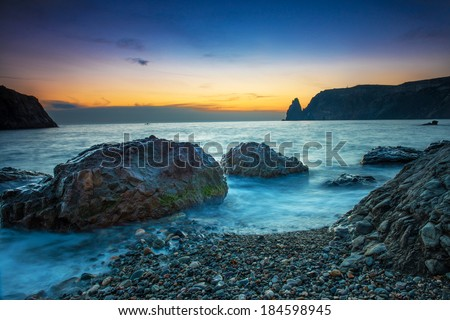 Sunset on the beach with sea, rocks and dramatic sky