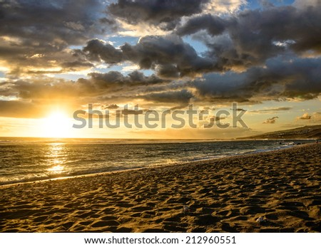 Sunset on the beach with spectacular clouds, la Reunion island - stock photo