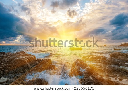 Sunset on the beach with waves, sea, rocks and dramatic sky. Landscape with sun in the centre - stock photo