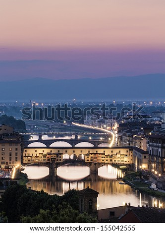Sunset on the beautiful city of Florence. In the foreground you can see the historic and famous Ponte Vecchio over the Arno River. - stock photo
