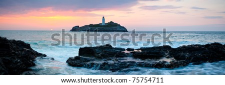 Sunset on the cliffs at Godrevy with Godrevy Island and Lighthouse in the background. - stock photo