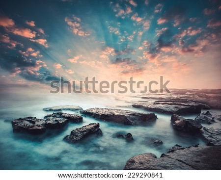 Sunset on the coast of the Sri Lanka at dawn with rocks in foreground - stock photo