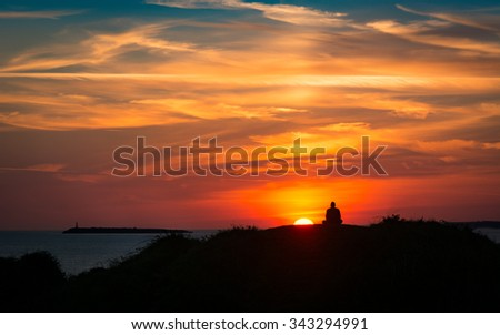 Sunset on the coast with a meditating man silhouetted against a colourful sky with clouds - stock photo